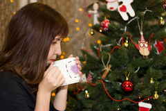 Girl drinks tea from a cup decorated christmas tree. Stock Photo