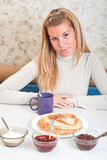 Girl drinks tea and eats russian pancakes. Young woman drinks tea and eats russian pancakes Royalty Free Stock Photography