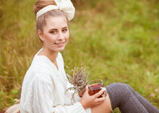 Girl drinks tea. Pretty young girl drinks tea in retro clothes, enjoying autumn day Stock Photography