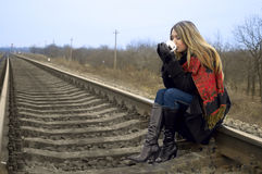 The girl drinks tea sitting on rails Royalty Free Stock Images