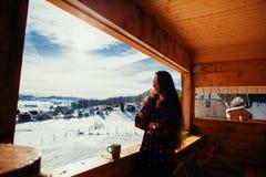 Girl drinks tea on winter terrace Royalty Free Stock Photo