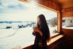 Girl drinks tea on winter terrace Stock Photo
