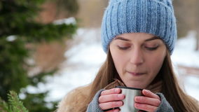 The girl drinks from a thermos near the trees stock footage