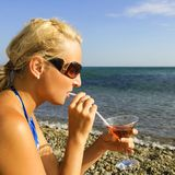 Girl drinks from tubule on beach. At the sea Royalty Free Stock Photo