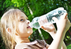 Girl drinks water. Little girl drinks water from a bottle Royalty Free Stock Photos