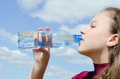 Girl drinks water against the sky Royalty Free Stock Images