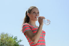 Girl drinks water against the sky Stock Image