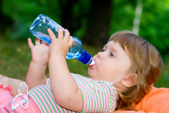 Girl drinks water from a bottle Stock Photos