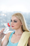 Girl drinks water from a bottle against the window. Royalty Free Stock Photography