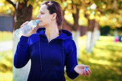 Girl drinks water from bottle in golden autumn park. woman drinks water after practicing yoga in city park stock images