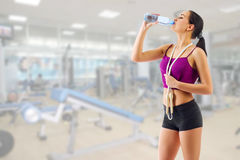 Girl drinks water at fitness club Stock Image
