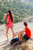 Girl drinks water on mountains. Girl drinks water on background of picturesque mountains Royalty Free Stock Photos