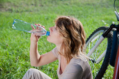 Girl drinks water near the bicycle Stock Photos