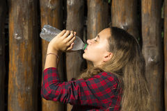 Girl drinks water from a plastic Stock Photos