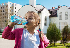 Girl drinks water from a plastic bottle Stock Photography