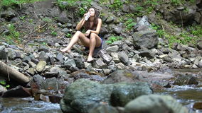 Girl drinks water on the shore of mountain river stock video footage