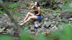 Girl drinks water on the shore of mountain river. Pure helpful water from mountain springs stock video footage