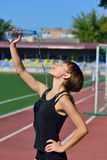 The girl drinks water at the stadium Royalty Free Stock Image