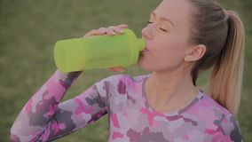 The girl drinks water after training at the stadium. The girl drinks water after training at the stadium stock video