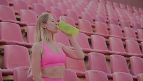The girl drinks water after training at the stadium. The girl drinks water after training at the stadium stock video footage