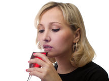 The girl drinks wine. The female drinks red wine from a glass Stock Photo