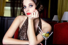 Girl drinks wine. The posing girl at restaurant in style old-fashioned Royalty Free Stock Image