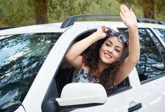 Girl driver inside car greeting somebody, look into the distance, has emotions and waves, summer season Royalty Free Stock Photography