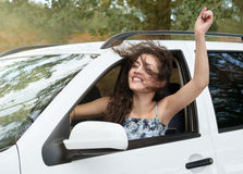 Girl driver inside car having fun, look into the distance, has emotions and waves, summer season Stock Photos