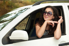 Girl driver inside car portrait, look into the distance through sunglasses, summer season Stock Photography