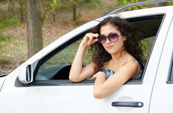 Girl driver portrait with sunglasses inside car Stock Image