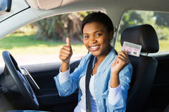 Girl driver's license. Cheerful african girl holding her driver's license she just got Stock Photos
