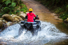The girl driving an ATV through the river Spree. Royalty Free Stock Photography