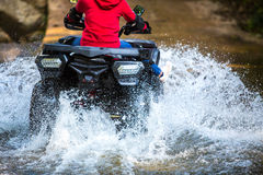 The girl driving an ATV through the river Spree. Royalty Free Stock Images