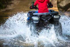 The girl driving an ATV through the river Spree. Royalty Free Stock Image