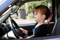 A girl driving a car. A girl about 5 years old is Drive an SUV Stock Photography