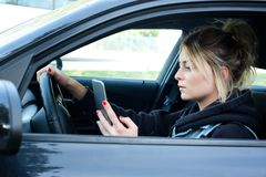 Woman driving car distracted by her mobile phone. Girl driving car and texting on her smart phone Royalty Free Stock Image