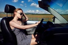 Girl driving a convertible car in a summer poppy field royalty free stock photos