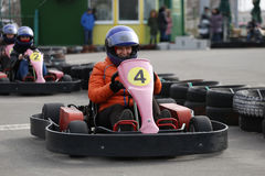 Girl is driving Go-kart car with speed in a playground racing track. Stock Photography