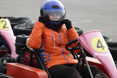Girl is driving Go-kart car with speed in a playground racing track. Royalty Free Stock Photo