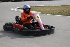 Girl is driving Go-kart car with speed in a playground racing track. Royalty Free Stock Photography