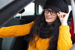 Girl driving her car. While touching her glasses Stock Photos