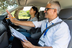 Girl driving instructor lessons. Smiling young girl with driving instructor taking lessons royalty free stock photos