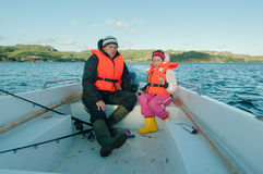 Girl driving the motorboat. Father giving a driving lesson to his daughter in a motorboat stock image