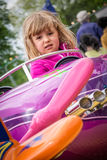 Girl driving toy car Royalty Free Stock Photo