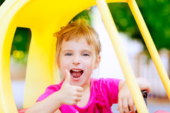 Girl driving toy car with ok hand gesture Royalty Free Stock Photos