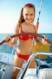 Girl driving a yacht Stock Photos