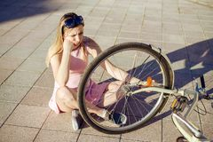 Girl dropped and broke the bicycle. emotion was frightened and does not know what to do stock images