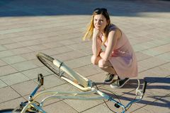 Girl dropped and broke the bicycle. emotion was frightened and does not know what to do stock photos