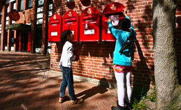 Girl dropping a letter in a red postbox Royalty Free Stock Images