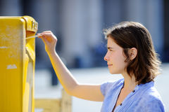 Girl drops a postcard in a mailbox in the Vatican Royalty Free Stock Images